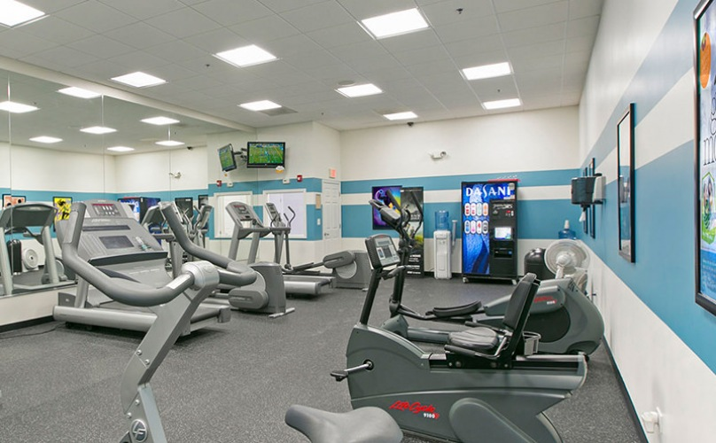 Fitness center has overhead lighting and mirrors